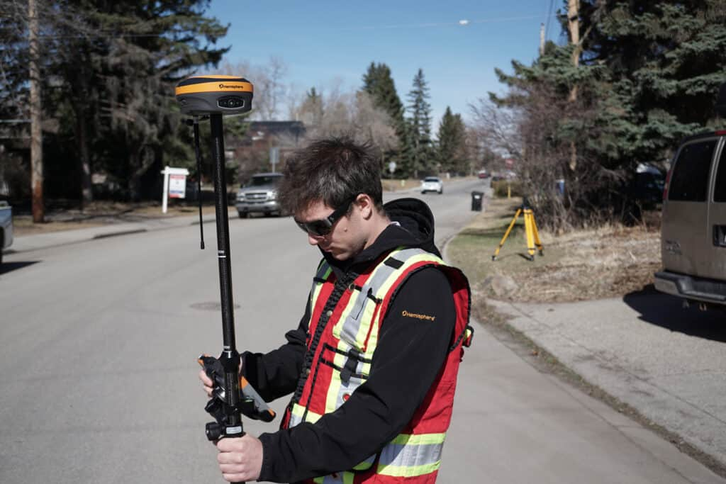 Man using GNSS equipment in the street. Specifically a Hemisphere S631 reciever.