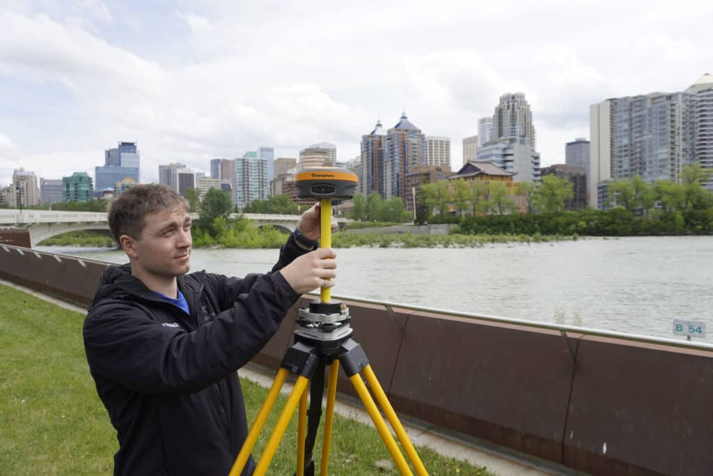 Man setting up GNSS equipment in front of river and downtown