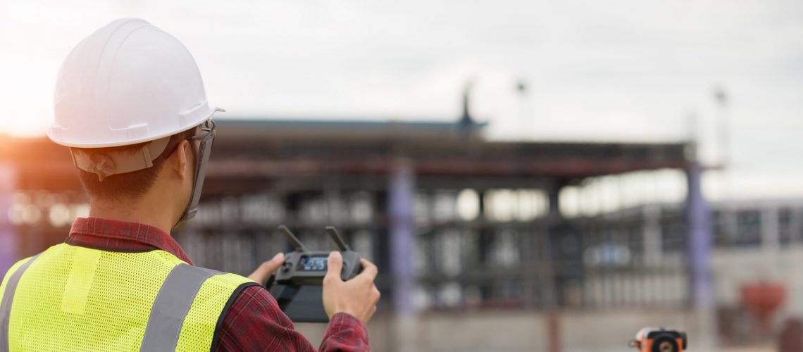 Engineer surveyor working with drone at construction site