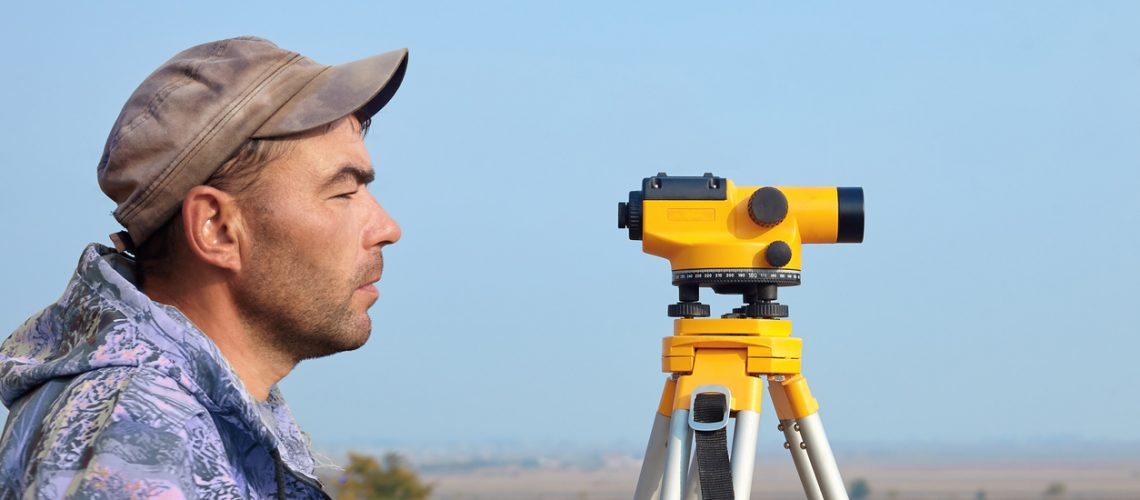 Worker with level, surveyor builder with geodesy equipment close to highway, with mobile phone.